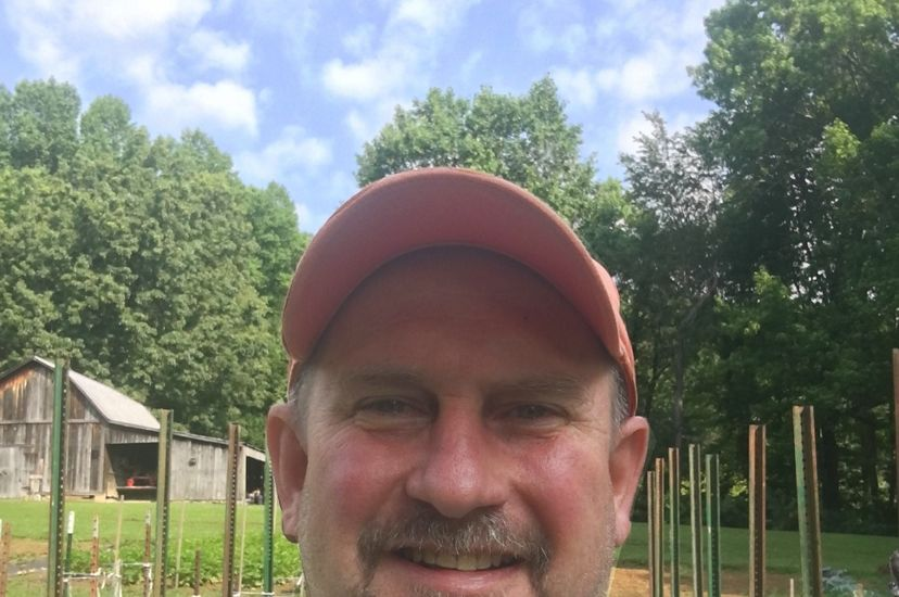 Candid headshot of Central Appalachians Forest Manager Mark Rogers. A smiling man wearing a baseball cap stands in front of a vegetable garden. Poles for vine beans are laid out in rows behind him.