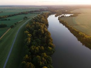 An aerial view of a river surrounded by forest and farmland.