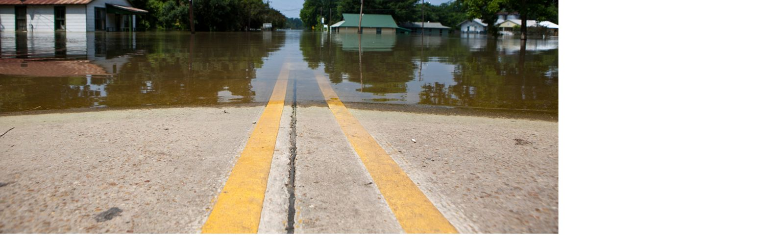 High water from mississippi river flooding a road with double yellow line in louisiana