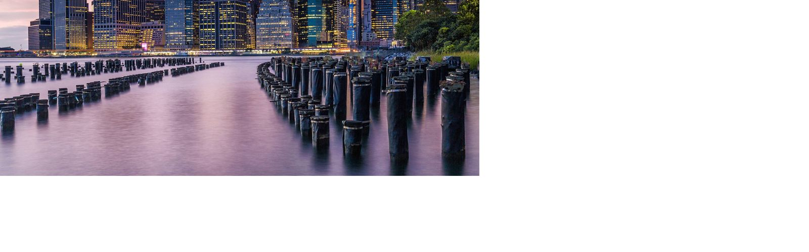 new york city manhattan skyline over east river with dock poles and bulkheads