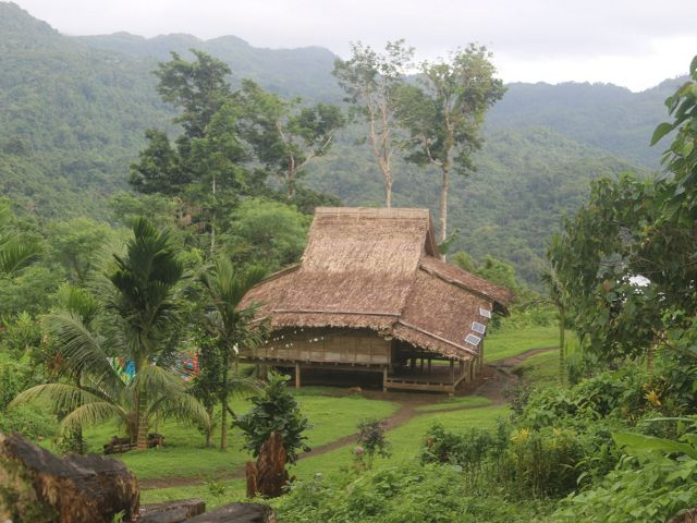 A typical house in a village in the Solomon Islands, with a roof made from Sago palm tree leaves and surrounded by lush forest and mountains.