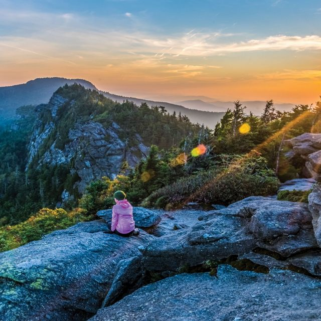 Frances experiences sunrise at Attic Window after camping on Grandfather Mountain ridge.  Ethan, Thanks, I'm honored to be included in the running. Here's the info you requested: Jim Magruder P.O. Box 154, Linville, NC 28646  Photo Caption: Grandfather Mountain Sunrise The photographer's wife Frances takes in sunrise from the Attic Window peak on Grandfather Mountain, North Carolina.  Through the combined efforts of The Nature Conservancy, the state of North Carolina, and the owners of Grandfather Mountain, Inc. Grandfather Mountain State Park was established in 2009 to preserve and protect Grandfather, one of the highest peaks in the Blue Ridge Mountains and one of the oldest mountains in North America. Grandfather Mountain is home to a wide variety of rare plants and animals and offers some of the most rugged and spectacular hiking in the eastern US.  This image is a two exposure HDR merge. One exposure for the sunrise sky and one for the rocky foreground. I cropped the merged HDR image to a panorama format to eliminate  some bland sky and rock at top and bottom.  Because of email size restrictions I am sending each of the 2 RAW files and the hi-res JPEG as attachments to separate emails.  Thanks, Jim