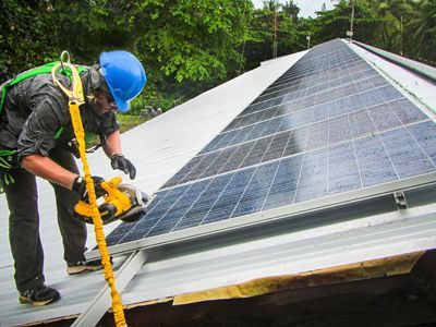 A worker harnessed on a roof installing a solar panel.