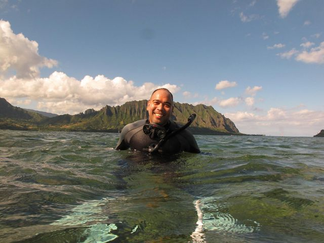 Man in the ocean in snorkel gear in chest height water with mountains in the background.
