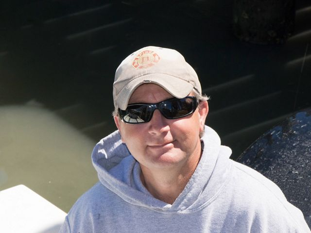 A man looking up at the camera from the deck of a small jonboat. He is wearing a gray hoodie and sunglasses. The sun reflects on the still water behind him.