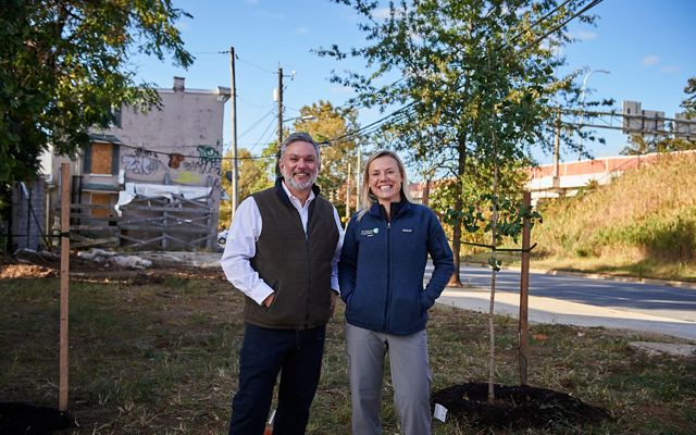 Vikram Krishnamurthy and Maria Dziembowska stand in a vacant lot that has been newly planted with trees.