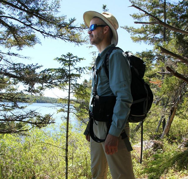 Mark Berry, TNC in Maine Forest Program Director, stands beside at lake near Spring River
