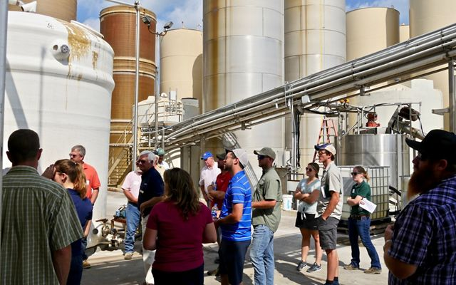 A group of people stand together listening to a presentation. They are surrounded by tall, narrow grain silos.