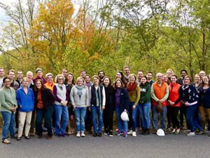 Group photo of TNC MD/DC staff. A large group of people stand together outdoors in front of a backdrop of trees, smiling during the chapter's annual staff retreat.