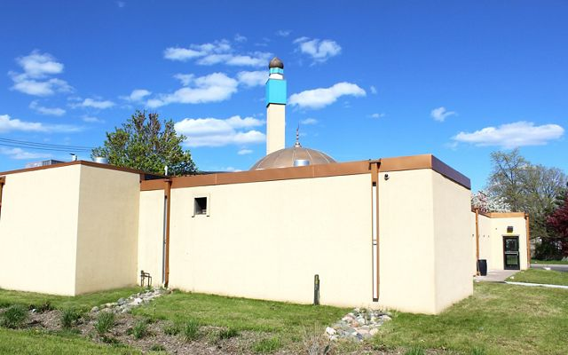 Back of the tan-painted Masjid An-Nur mosque building with bioswale (rain garden) in the foreground.