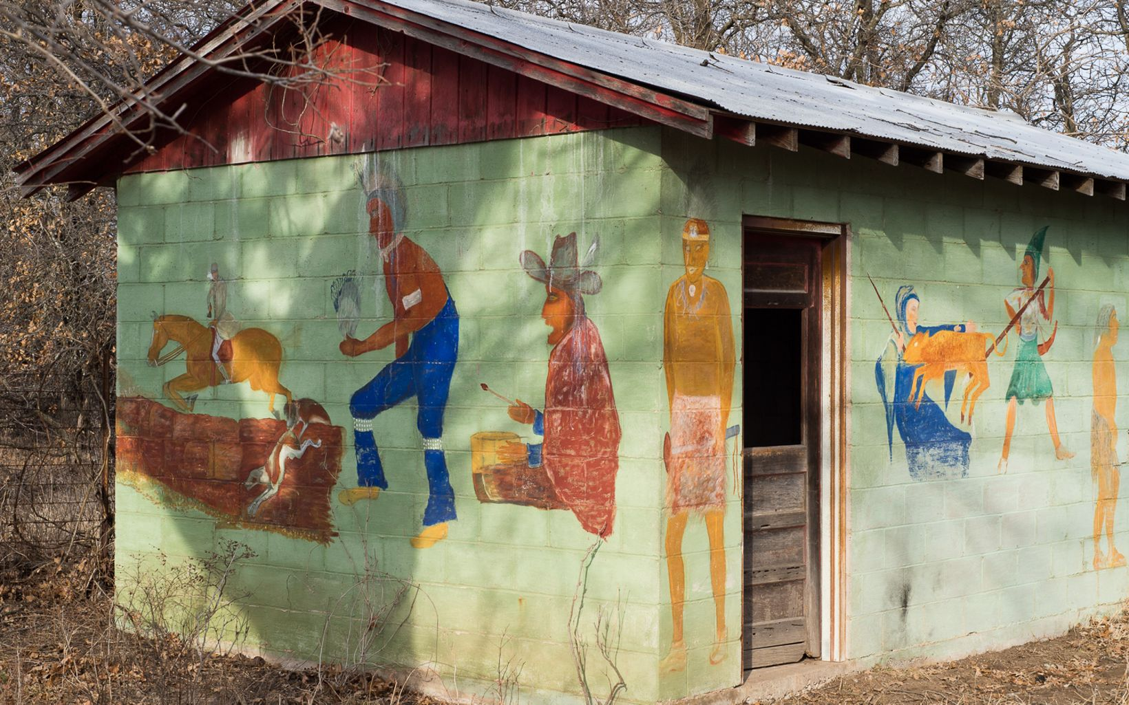 Mathews painted his depiction of the history of man on his outbuilding near the cabin.