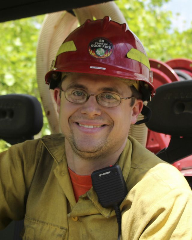 """A smiling man wearing a red hard hat and yellow fire protection gear during a controlled burn.. A sticker on his helmet reads """"Good Fire"""" and shows the TNC globe logo surrounded by flames."""