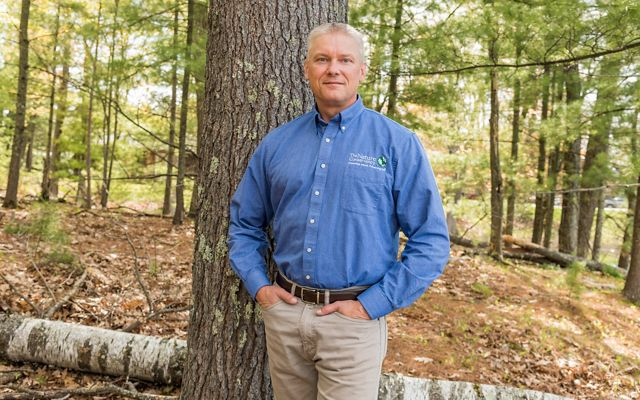 Deputy State Director Matt Dallman poses in front of a tree with a downed birch tree at his feet in an open Northwoods forest.