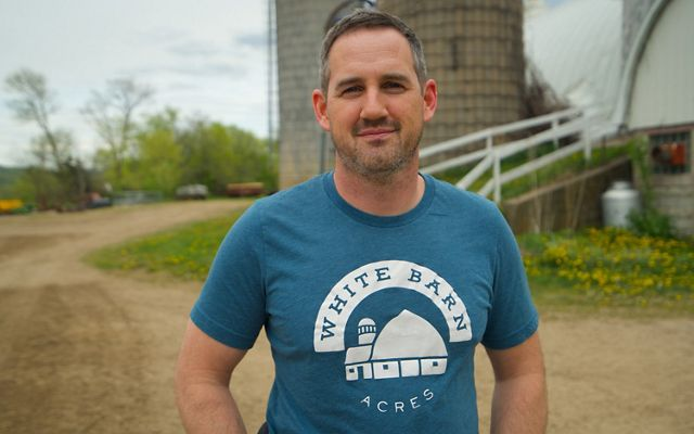 Matt Tentis standing in front of his family farm's barn wearing a t-shirt that reads White Barn Acres.