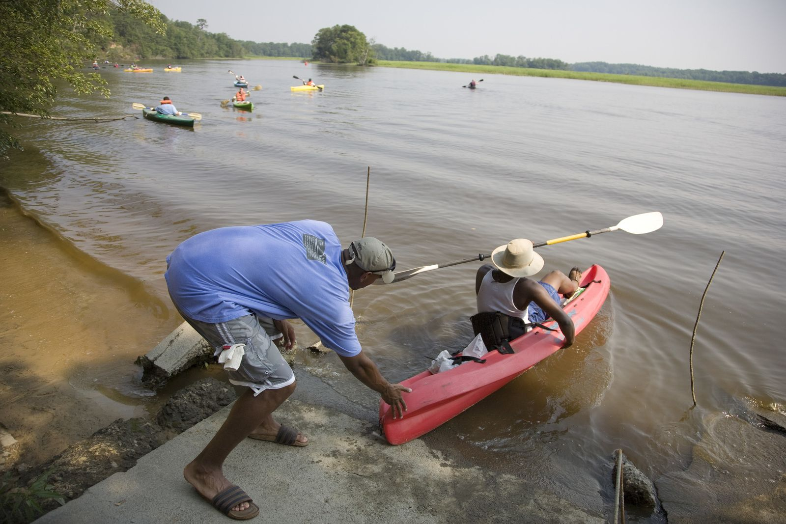 Preserve visitors are pushing their kayaks off of the shore.