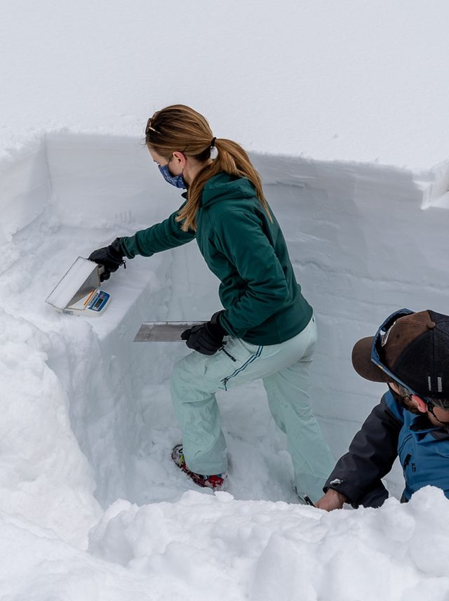 A woman and man taking snow samples in a dug-out snow pit.