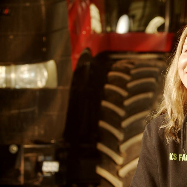 A woman sitting in front of a red tractor.