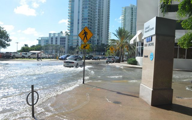 A car drives through standing water in an intersection in the Brickell neighborhood in Miami.