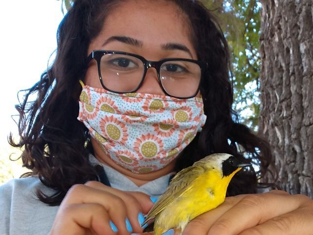 Young woman in with dark-framed eyeglasses and colorful face mask holds bright yellow bird.