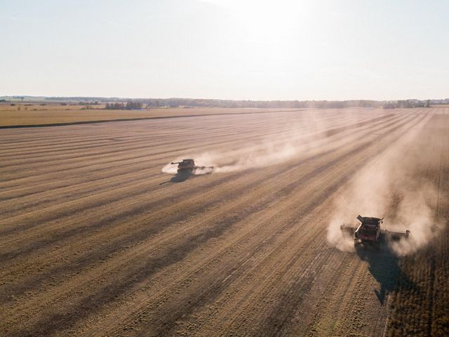 Aerial view of two tractors kicking up dust in a field.
