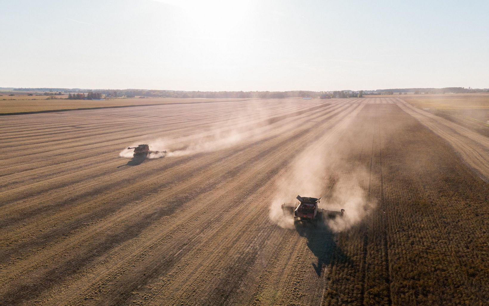 Aerial photo of two tractors moving through a field.