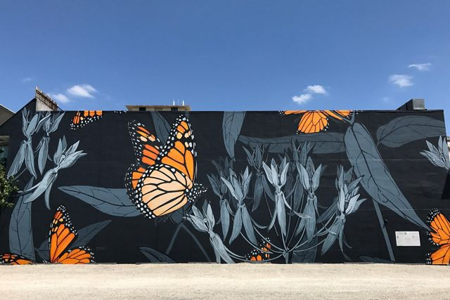 The side of a building is painted with bright orange monarch butterflies on a black background with gray leaves and flowers.