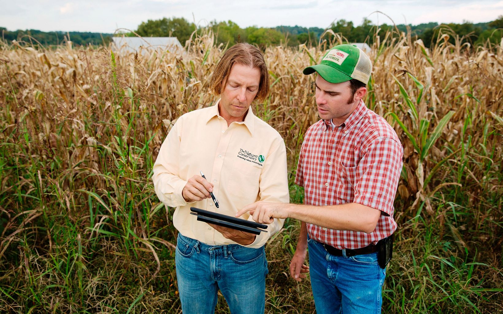 A farmer and TNC employee look at a tablet.