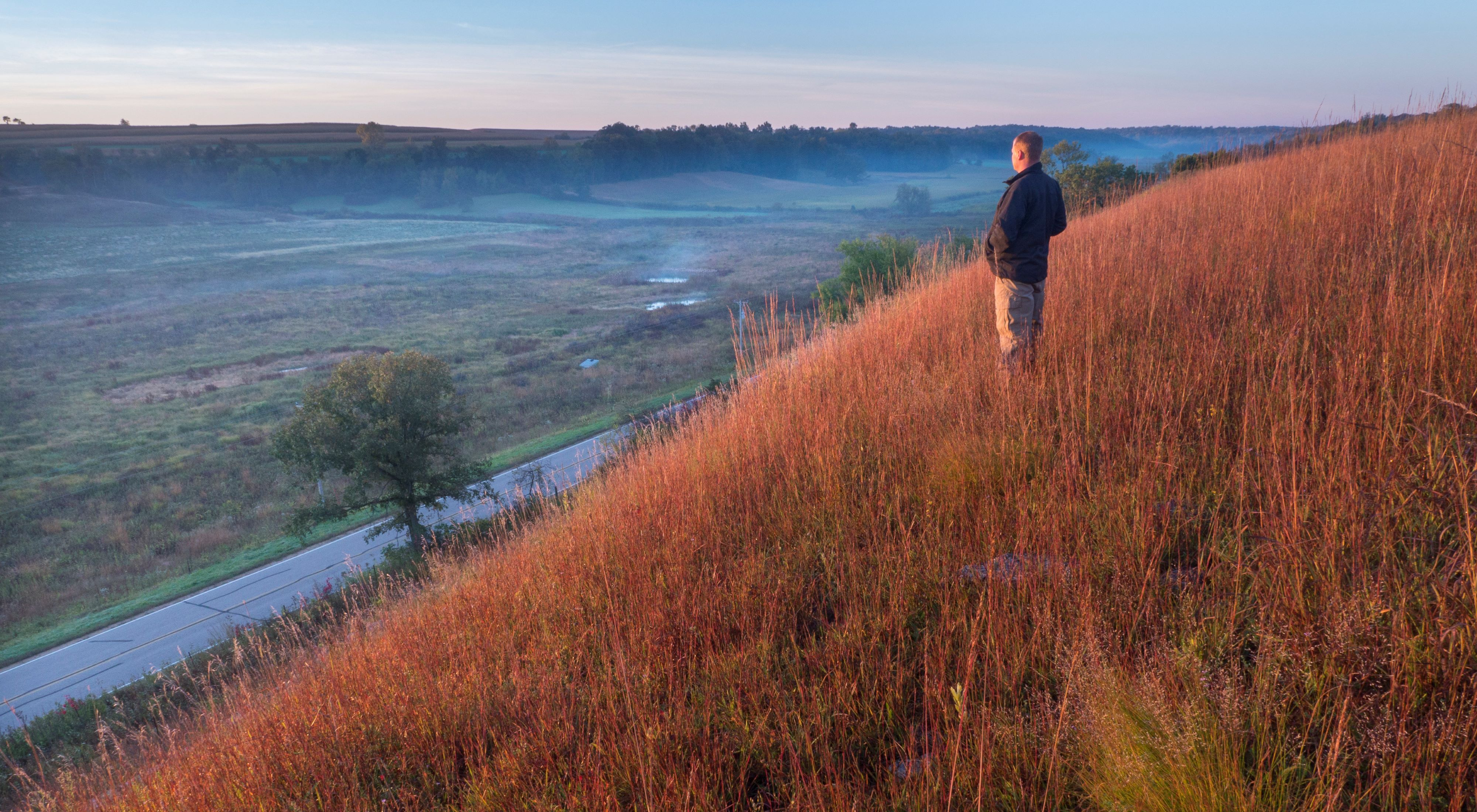 Man stands in a hillside prairie on a hillside overlooking a valley with hills in the distance as the sun sets.