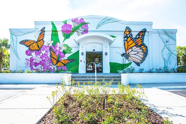 The front of a white building is painted with huge monarch butterflies sitting on plants with green leaves and bright pink flowers. Shrubby plants grow along the front of the building.