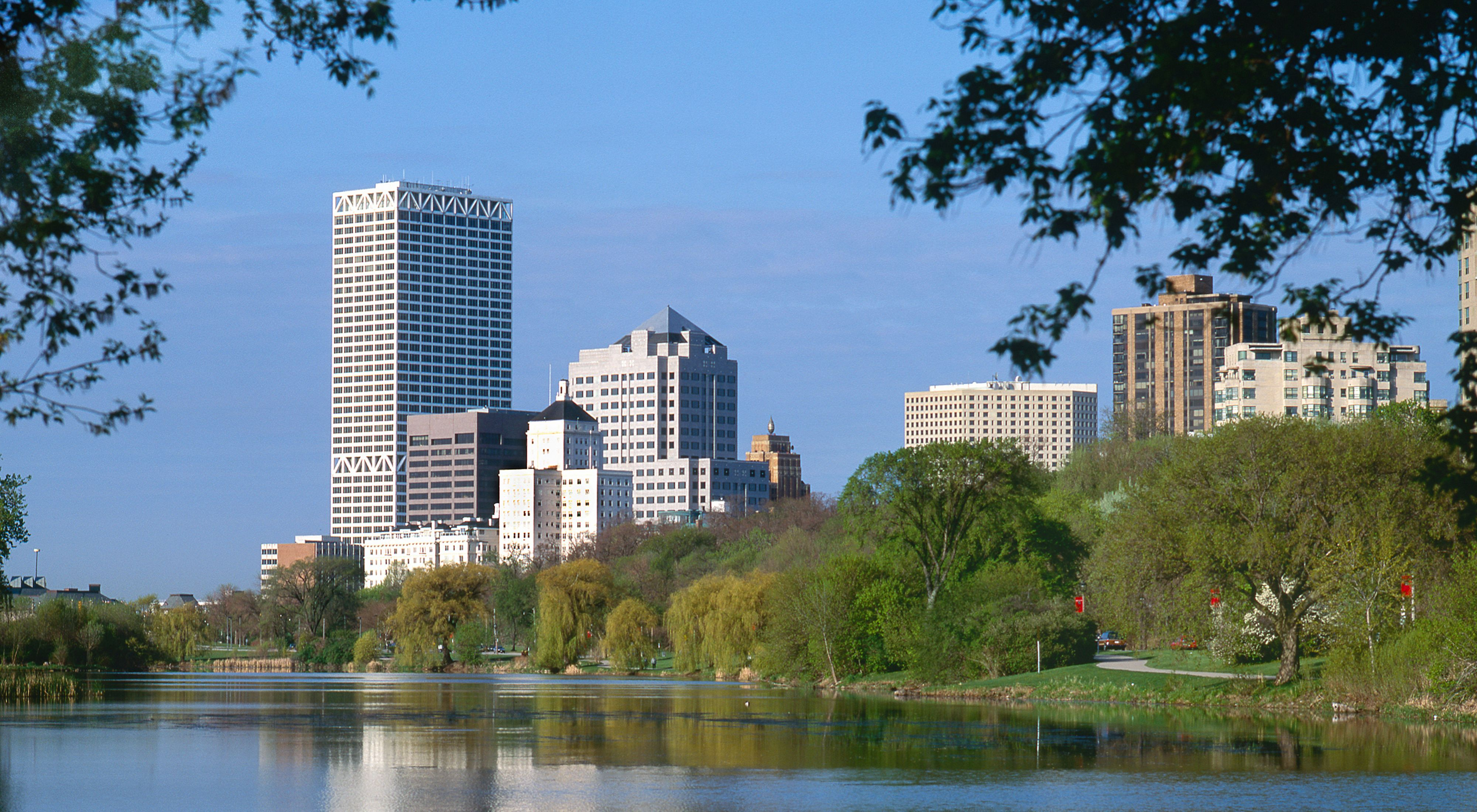 View of a city skyline with tall buildings in the background and trees and grass along the shoreline of a small lake.
