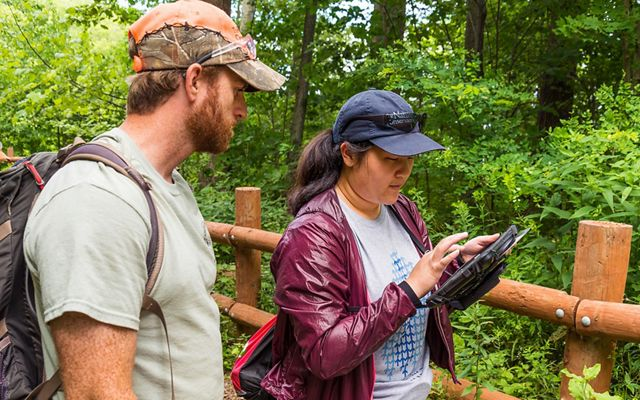 Young woman on a trail in a park types something into an iPad she is holding while man wearing a backpack and baseball cap looks on.