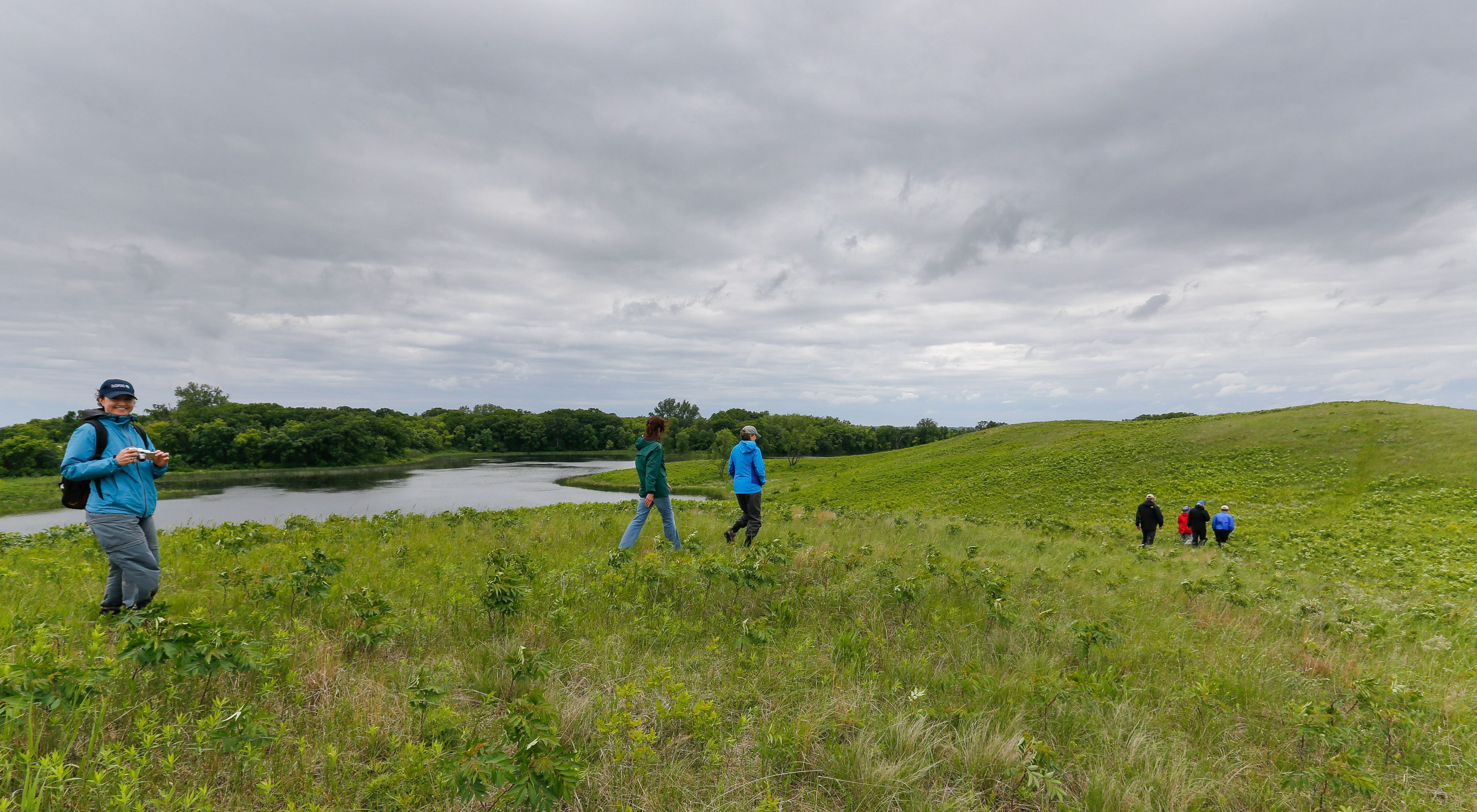 People hiking on a green, rolling prairie alongside a pond at  Northern Tallgrass Prairie National Wildlife Refuge.