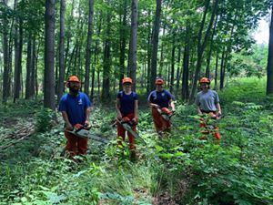 Fie Thao, Gabbi Genz, Karina Cardella, and Bobbi Rooney stand in a row in the middle of a green forest, each holding a chainsaw and wearing protective gear, all smiling.