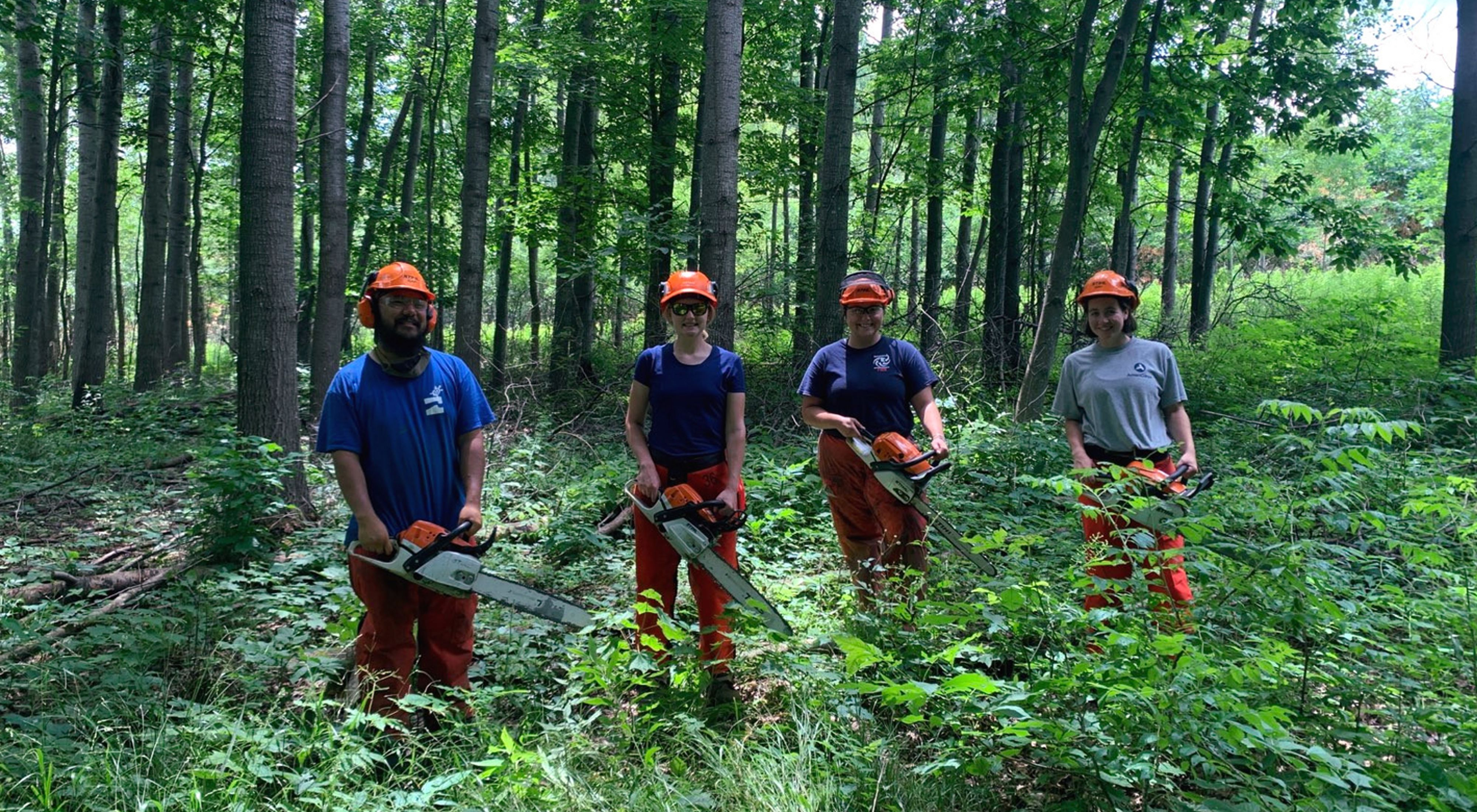 Fie Thao, Gabbi Genz, Karina Cardella and Bobbi Rooney stand in a row in the middle of a green forest, each holding a chainsaw and wearing protective gear, all smiling.