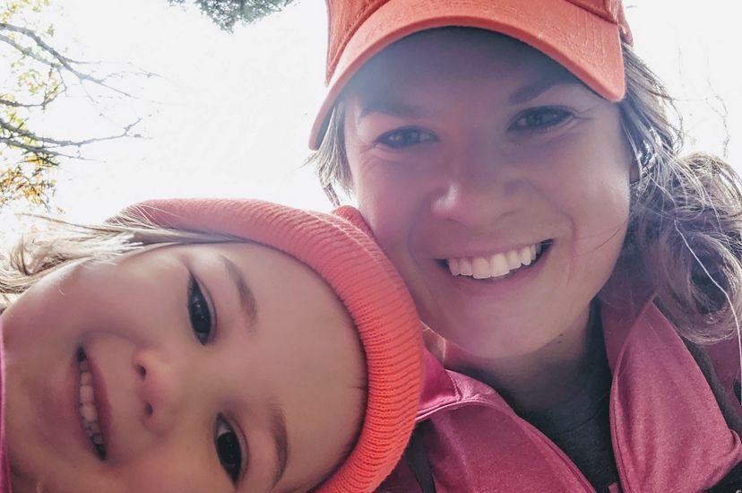 Molly Payne Wynne y su joven hija en pie entre varios árboles se toman un retrato cercano a sus rostros.
