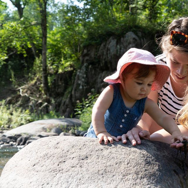 TNC fisheries scientist shows her young daughter how to inspect rocks along a river.