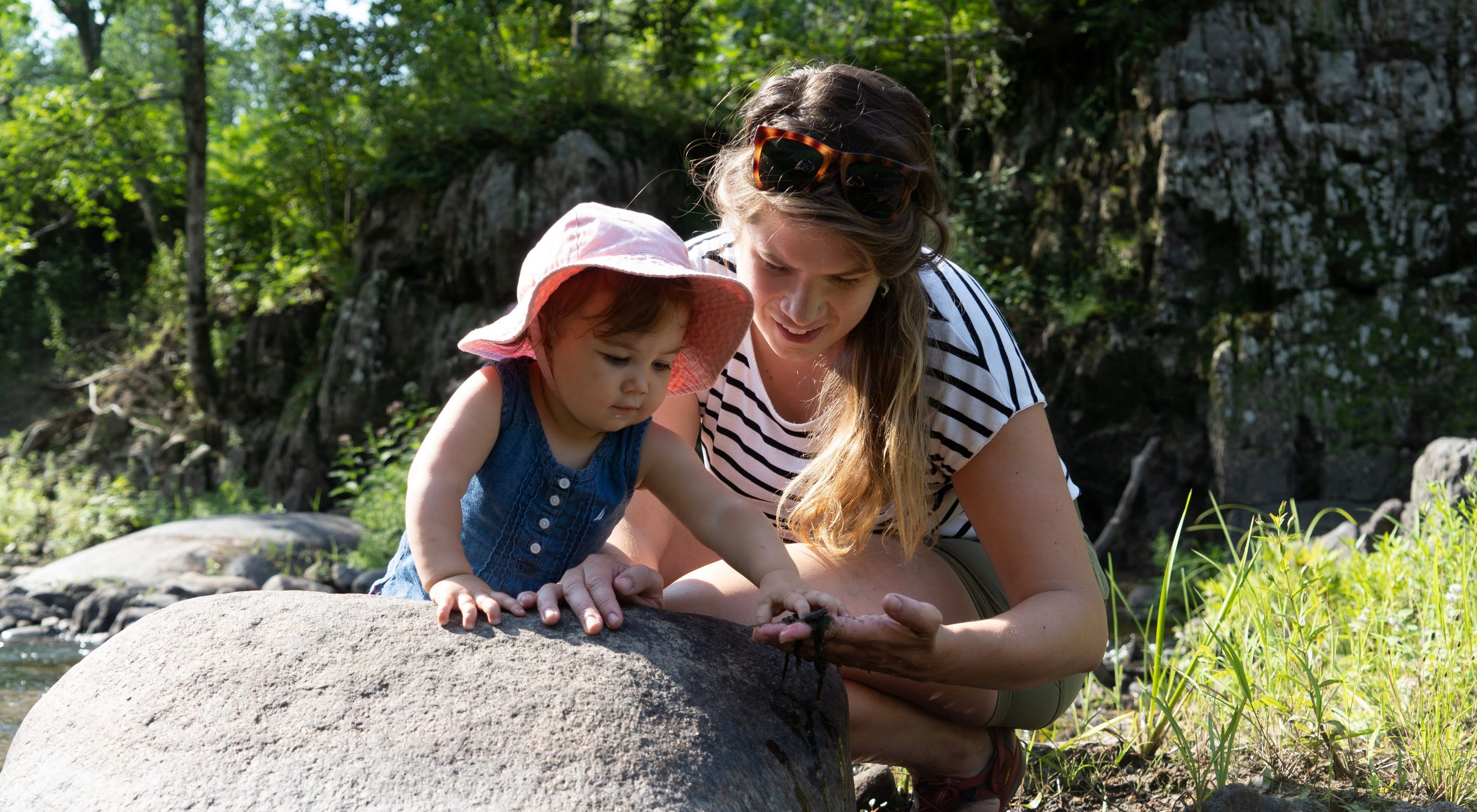 Una científica de TNC le enseña a su joven hija a inspeccionar rocas a la orilla del río.