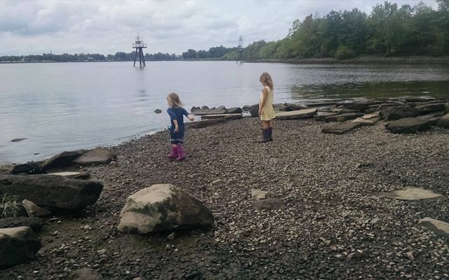 Two young girls wearing rubber boots explore the shoreline of a marsh. One girl has her arm pulled back ready to throw a rock into the water.