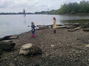 Two young girls wearing rubber boots explore the shoreline of a marsh. One girl has her arm pulled back ready to throw a rock in the water.