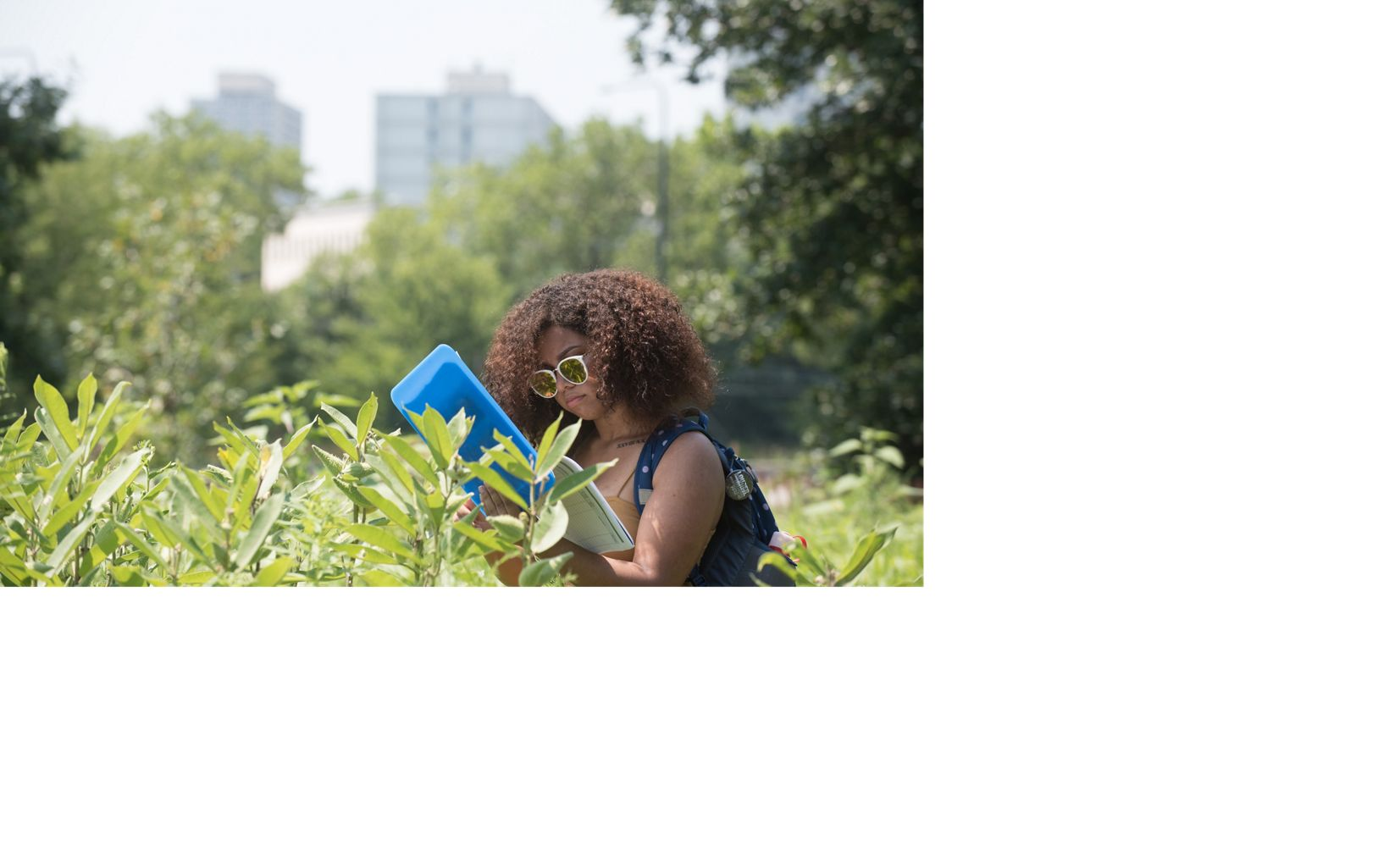 a woman with a blue clipboard surrounded by tall green plants
