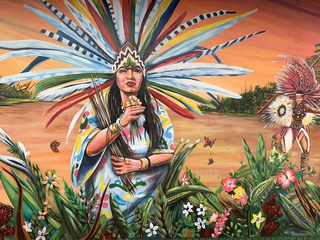A mural shows two people wearing headgear and clothing decorated with long, colorful feathers, representative of Mexican indigenous cultures. Several painted butterflies fly over flowers.