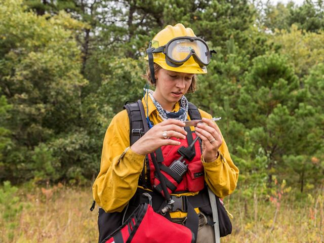 Birch Malotky uses an instrument to calculate relative humidity during a controlled burn at Kennebunk Plains Preserve.
