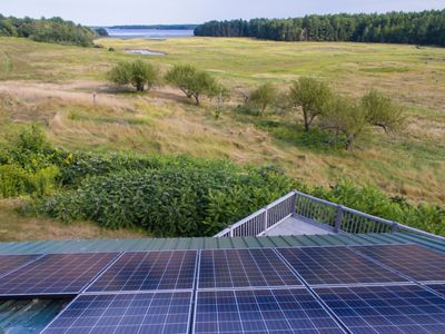 Solar panels on the roof of an office overlooking water.