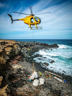A yellow helicopter hovers over a rocky beach to pick up large white bags of debris as tiny people wave from below.