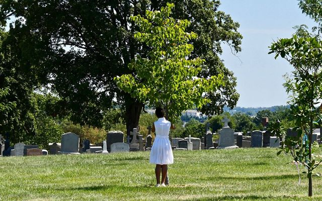 Tying a prayer ribbon to a tree at Mount Olivet Cemetery during a celebration of the legacy of freedmen John and Arabella Weems.
