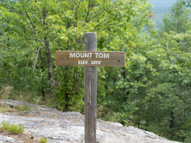 A wooden summit sign on a signpost reads Mount Tom elev. 1,073.