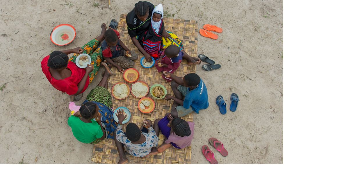 Family eating a meal on a mat on ground