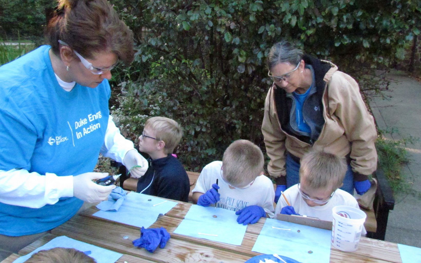 Duke Energy employees help schoolchildren tag mussels as part of TNC's mussel reintroduction program.