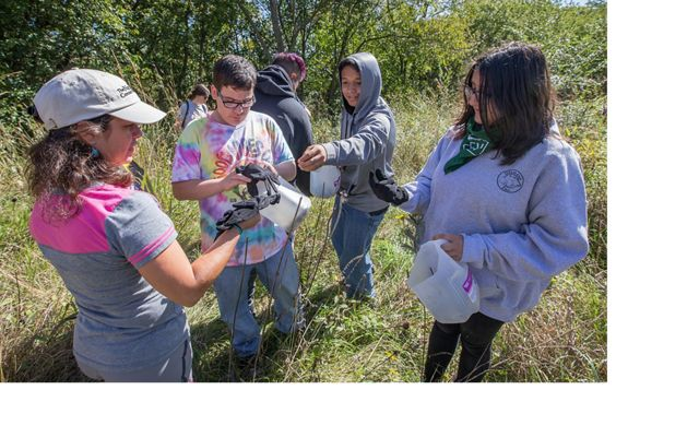 TNC Cities Conservation Fellow Lainet Garcia Rivera helps a group of 5 students from Milwaukee's Escuela Verde