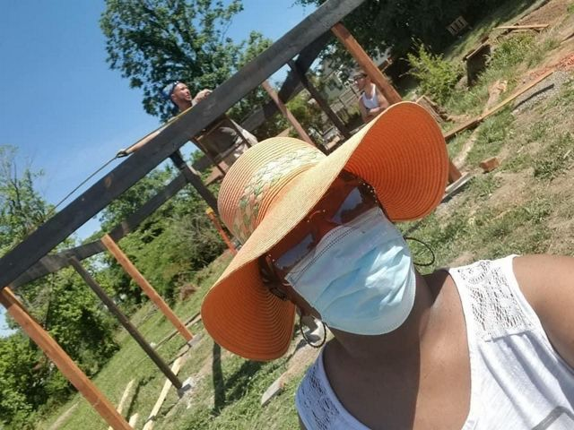 A woman in an orange straw hat, mask and sunglasses stands in front of an urban farming project.